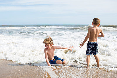Brothers enjoying at beach against sky during sunny day - p1166m1404077 by Cavan Images