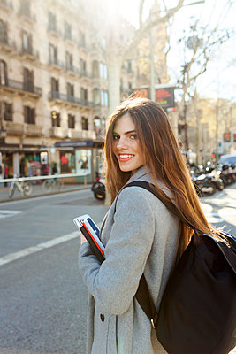 Spain, Barcelona, portrait of smiling young woman with backpack standing at street - p300m1587065 by Valentina Barreto