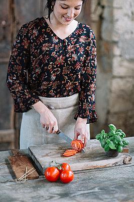 Woman preparing Caprese Salad - p300m2012392 von Alberto Bogo