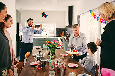 Man photographing boy with family during birthday party through smart phone - p426m1580223 by Maskot
