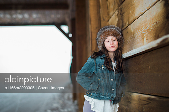 Girl in fur headband leaning against a bridge with eyes closed - p1166m2200305 by Cavan Images
