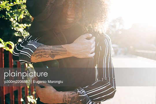 Loving couple embracing while standing in park on sunny day - p300m2206887 by Eugenio Marongiu