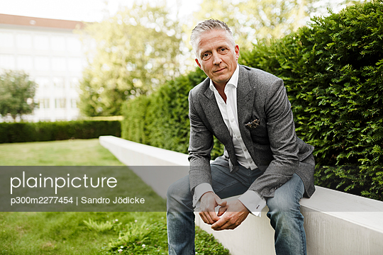 Confident businessman sitting on retaining wall - p300m2277454 by Sandro Jödicke