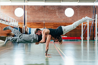 Full length side view of gymnasts practicing handstand at gym - p1166m1561446 by Cavan Images