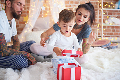 Surprised boy opening Christmas present with his parents in bed - p300m2041609 von gpointstudio