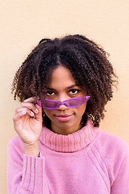 Portrait of young woman wearing pink turtleneck pullover and purple sunglasses - p300m2070373 by Lucas Ottone