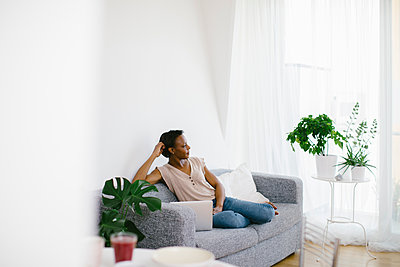 Woman sitting on couch at home with laptop - p300m2121824 by Sofie Delauw
