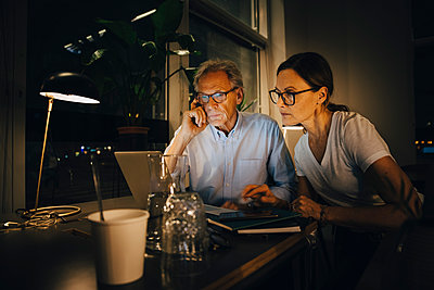 Businesswoman with senior businessman planning strategy in dark office while working late - p426m2194839 by Maskot