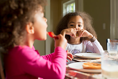 Mixed race girls eating breakfast - p555m1479186 by Inti St Clair photography