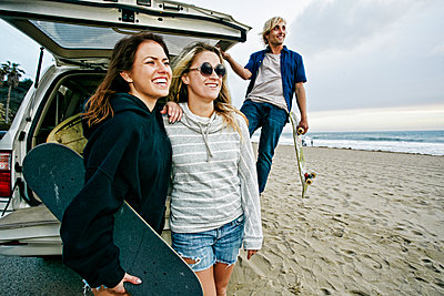 Caucasian friends near car hatch at beach holding skateboards - p555m1491134 by Peathegee Inc