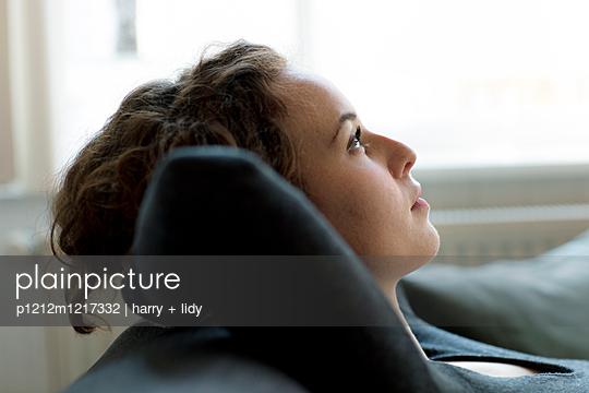 Junge Frau enstpannt sich auf dem Sofa - p1212m1217332 von harry + lidy