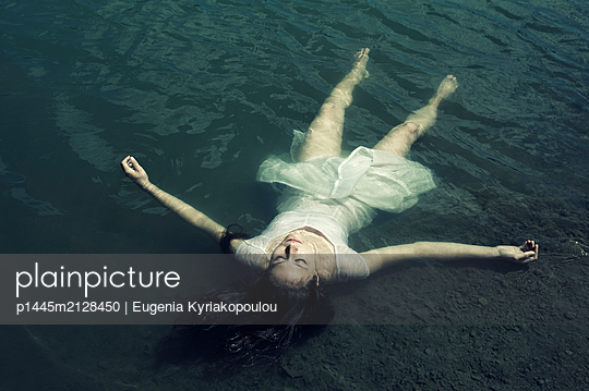 Young woman floating in water - p1445m2128450 by Eugenia Kyriakopoulou