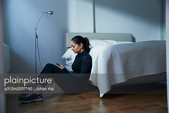 Woman sitting on bedroom floor and using phone - p312m2237190 by Johan Alp