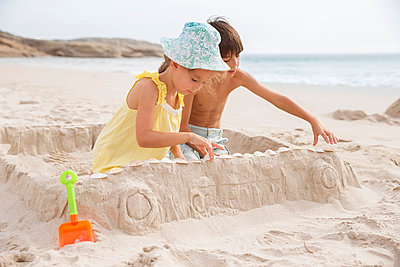 Children making sandcastle on beach - p1023m857726f by Robert Daly