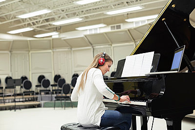Female student playing piano in college music room - p1192m1043849f by Hero Images