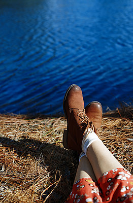 Legs of the woman relaxing next to the lake - p1577m2175355 by zhenikeyev