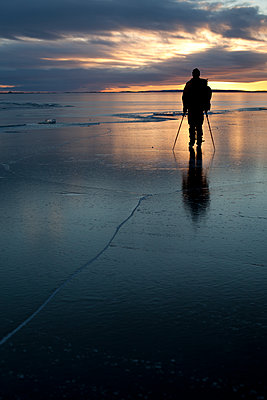 Sweden, Silhouette of a man ice skating in the evening light - p1687m2284304 by Katja Kircher