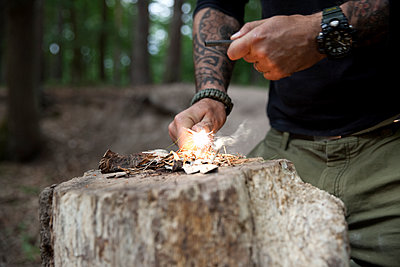 Man igniting a fire on tree stump in the forest - p300m1499520 by Michelle Fraikin