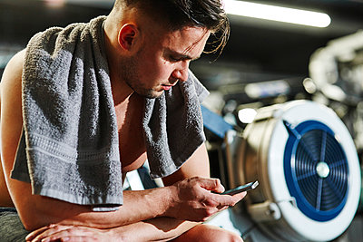 Man using cell phone at the gym - p300m1581568 by gpointstudio
