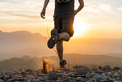 Spain, Barcelona, Natural Park of Sant Llorenc, man running in the mountains at sunset - p300m2058585 von VITTA GALLERY