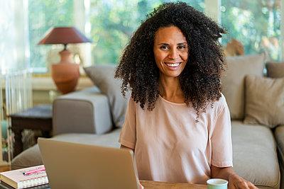 Smiling female entrepreneur sitting in living room at home - p300m2250338 by Annika List