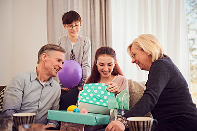 Family looking at smiling girl opening gifts on sofa at home - p426m1580240 by Maskot
