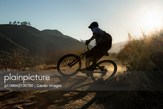 Mature Man riding mountain bike on trail in San Diego, California - p1166m2130750 by Cavan Images