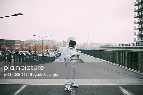 Astronaut using digital tablet on ramp - p429m2091381 by Eugenio Marongiu
