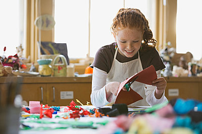 Girl cutting paper in art class - p1192m1023930f by Hero Images