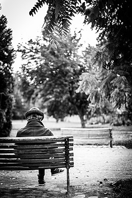 Man seen from behind sitting on a bench in a park - p1682m2260725 by Régine Heintz