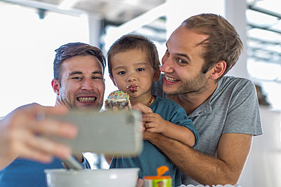Gay couple baking cake with son - p300m1028784f by zerocreatives