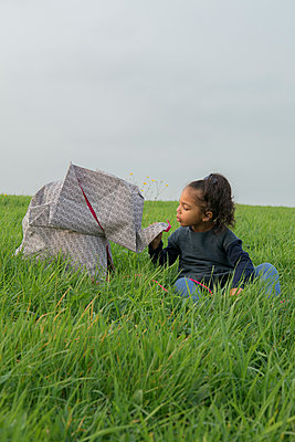 Little girl with origami elephant on meadow - p300m2012941 von Petra Stockhausen