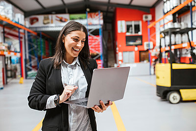 Smiling female manager using laptop in illuminated distribution warehouse - p300m2266649 by DREAMSTOCK1982