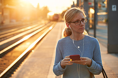 Woman using cell phone at train station - p312m2207918 by Johan Alp