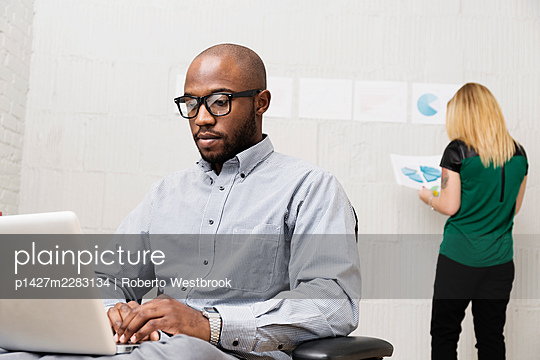 Business partners working in design office - p1427m2283134 by Roberto Westbrook
