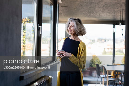 Smiling woman with coffee cup looking through window while standing at home - p300m2265100 by Emma Innocenti