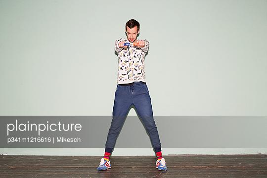 Junger Mann mit Wasserpistolen - p341m1216616 von Mikesch