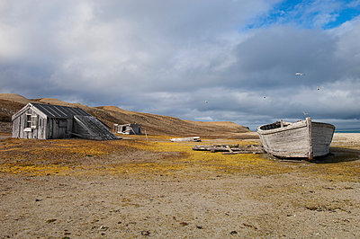 A small log cabin, a fishing hut with a beached boat. - p1100m923415f by David Schultz