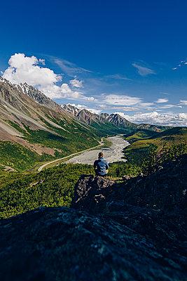 Person sitzt auf einem Stein mit Gebirge im Hintergrund - p1455m2204831 von Ingmar Wein