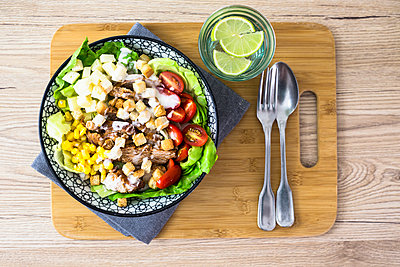 Bowl of Caesar salad with meat, corn and tomatoes - p300m2023478 by Giorgio Fochesato