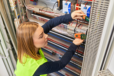 Female electrician working with voltmeter at fuse box - p300m2181231 by Zeljko Dangubic