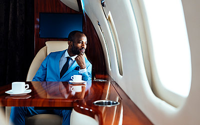 Young businessman with hand on chin looking through window while sitting in private jet - p300m2256365 by OneInchPunch