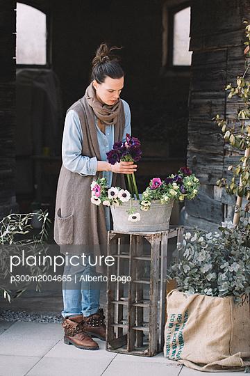 Woman arranging fresh flowers - p300m2004665 von Alberto Bogo