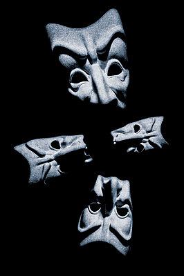Four tragedy face masks arranged on black background - p1047m2228928 by Sally Mundy