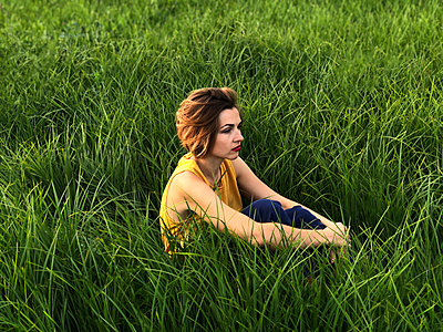 A young woman in a yellow blouse is sitting in a green field. - p1166m2112030 by Cavan Images