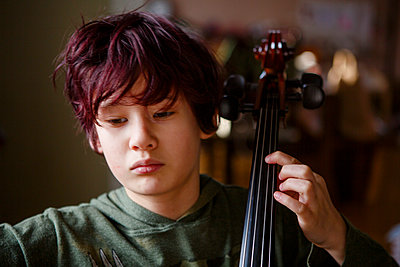 Close-up of serious boy with dyed red hair practicing cello music - p1166m2246521 by Cavan Images
