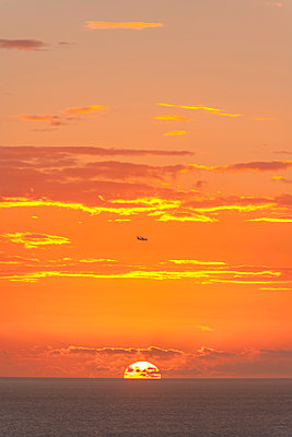 Polynesia, Sunset over the pacific ocean in Tahiti with a plane  - p1487m2253933 by Ludovic Mornand