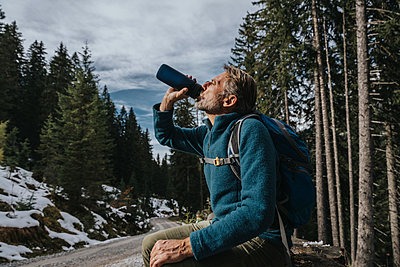 Male tourist drinking water while sitting against trees at Salzburger Land, Austria - p300m2267470 by Mareen Fischinger