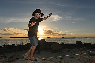 France;  Bretagne;  Landeda;  Man balancing on slackline on beach - p300m838548f by Albrecht Weißer