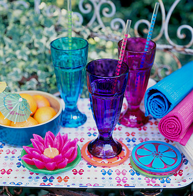 Coloured glassware and crockery on a table in the garden - p349m695234 by Emma Lee